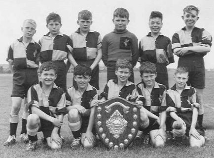 The School football team for 1957/8 in our gold and black school shirts, some with a gold eagle. We have the shield for the local school competition. Does anyone recognise themselves? I am on the far right front row. Some of the names escape me, but from memory: Back row Steve Ballard, Terry Martin, Doug Wilson, Mick Salisbury, Philip Jones, John Durrant Front row Johnny Peters, Richard Bashford, Tony Idle, Michael Hough and me Peter Gillard. Uploaded byPeter Gillard
