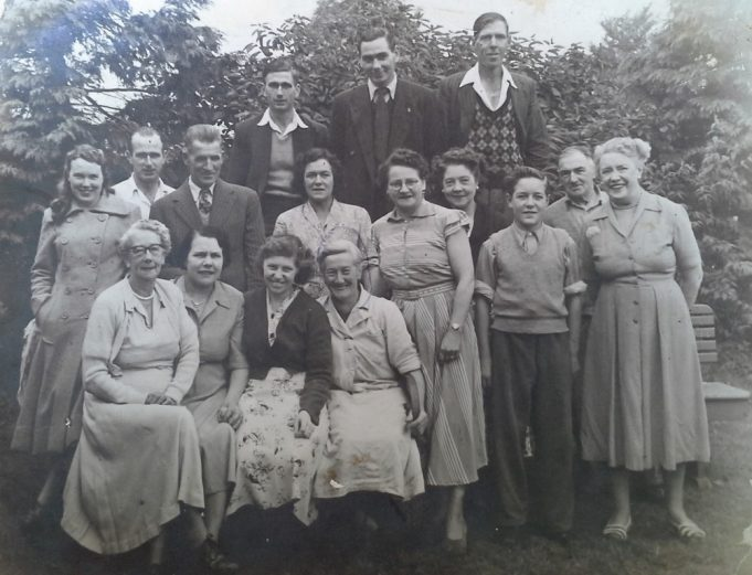 The staff of the Tarpot Pub, this picture is thought to be taken 1944.  The Landlady Mrs Wright is in the front row seated far left,  Edie Rogers barmaid is seated front row far right.  James Ferguson second middle row, father of George Ferguson, 2nd left back row and Alex Ferguson 3rd left top row.  It is thought the young boy is Bobby Bashford.  For more names see comments below. | Ernie Rogers
