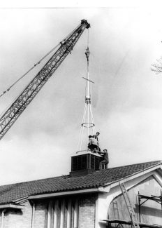 Rev'd Carlos standing far side of fleche when it was positioned on the roof, 1964.
