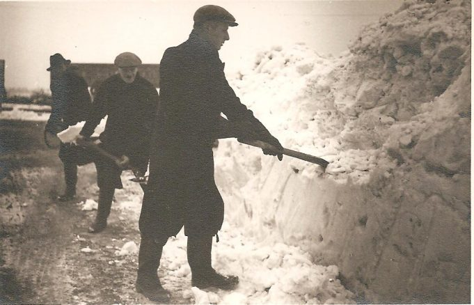 A group of unidentified men tackling the snowdrifts on shore.