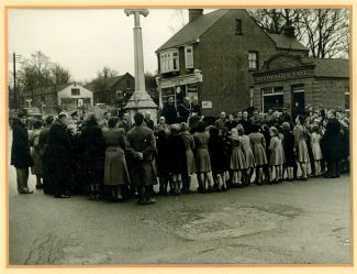 A gathering at the War Memorial and in the background The Clock House Cafe  c.1952 | Castle Point Council