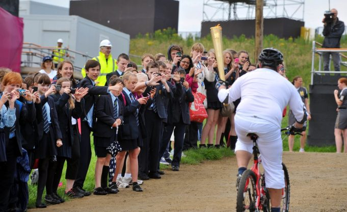 Dan Jarvis riding with the Torch past school children | Nick Strugnell