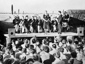 Geraldo and his orchestra, fronted by the singer Dorothy Carless, entertain airmen at an airfield in North Africa, 1943. | This is photograph CM 5442 from the collections of the Imperial War Museums