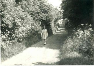 Eileen walking down Hill Road, taken in the late 1950s.  In the distance is the entrance to 'Jarvis Hall' | Harry Emery