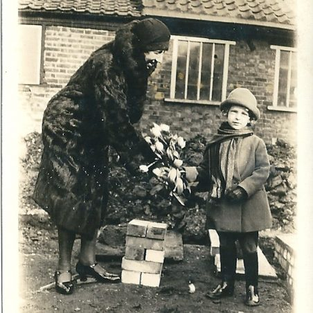 Joan Phillips (nee English) presenting her grandmother with flowers. | Joan English
