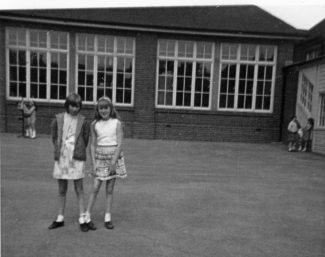 This photo was taken in the playground of Benfleet Primary School. The girl with the long hair (it was a beautiful golden/red blonde !) holding her skirt is Jenny Smith, she was in the year above me at school but we were best friends after meeting in our shop, she lived in Hall Farm Road at the time. I think the other girl was called Clare. c. mid 1960s. | Stephanie File