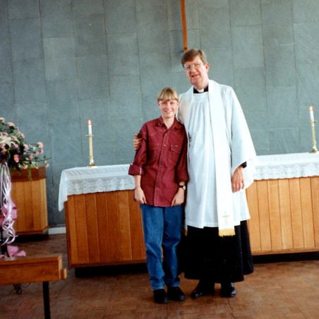 John Kemp at the altar with young member of the church.