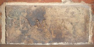 Half brick incised with the letters RAM AY