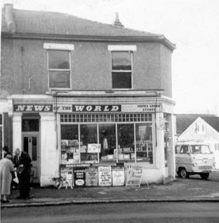 Our shop front, then called Hopes Green Stores.  My dad is standing outside talking to a customer. The dog is our little brown and white mongrel who was named Nicky. | Stephanie File