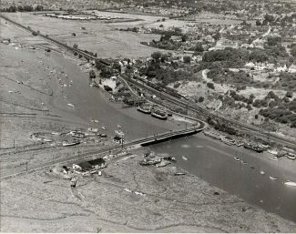 Aerial view of Benfleet Creek taken in 1948, the yacht club at this time can be seen moored close to the railway station.  The bridge across the creek opened to allow boats to go out into the Thames Estuary