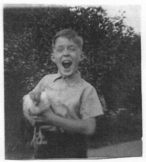 Holding my pet chicken which was eventually taken by a fox. 1954 | John Garnham