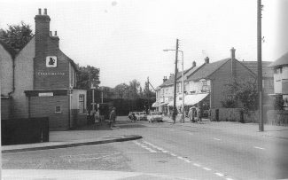 Hart Road with the White Hart Public House on the left. The first shop with the pull down sun blind was the fish and chip shop.  c.1960s