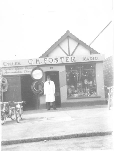 G. H Foster, 115 - 117 High Road. Mr George Foster stands in front of his shop (now demolished). Elora Chemist occupies this position today. The number 19 on the shop facade is misleading and may refer to when the High Road was the London Road. | Ralph & Joan Pickett