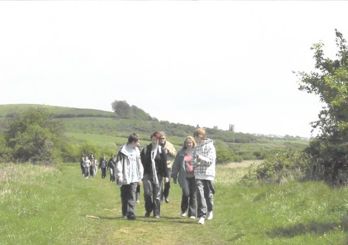 Walkers on The Benfleet Downs with Hadleigh Castle in the background.