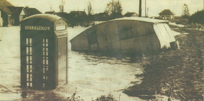 Misery - a telephone box, a caravan and houses, seen in the background, are submerged by flood water. | Echo supplement 29 Jan 2003