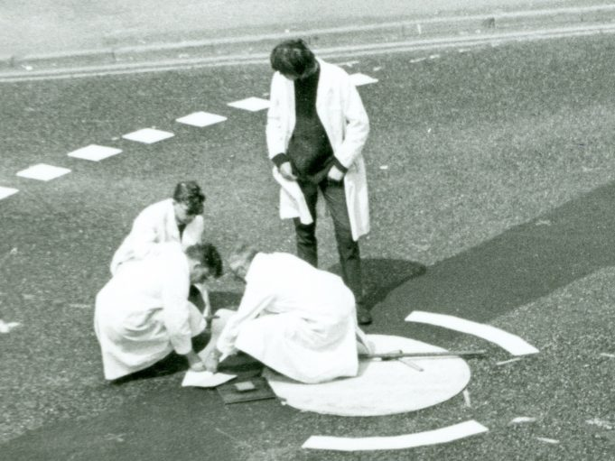 This part of a photo shows the four members of the Road Research Laboratory team laying down an arrow. The older member sitting on the centre we presume to be Frank Blackmore. | CPDC