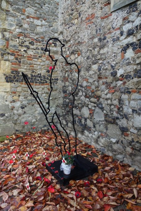St Mary's Church Tommy on field of fallen leaves with Poppies